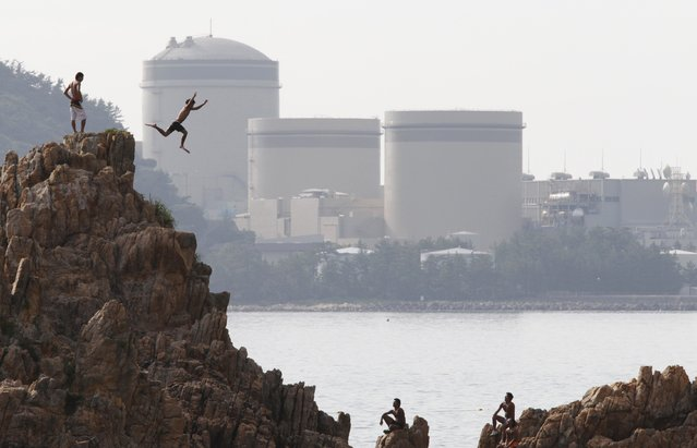 A man on vacation dives into the sea as Kansai Electric Power Co.'s Mihama nuclear power plant is seen in the background in Mihama town, Fukui prefecture, in this file picture taken July 2, 2011. (Photo by Issei Kato/Reuters)