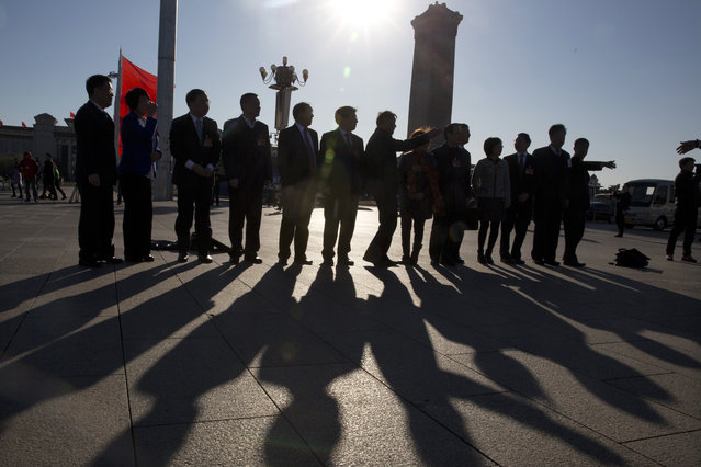 In this photo taken Sunday, March 12, 2017, participants arrive near the Great Hall of the People where a plenary session of the National People's Congress is held in Beijing, China. (Photo by Ng Han Guan/AP Photo)
