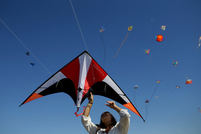 A woman lets a kite go airborne during an international kite festival in Alcochete, near Lisbon, Portugal, Sunday, June 28, 2015. (Photo by Francisco Seco/AP Photo)