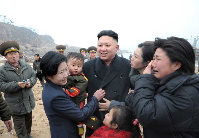 Residents greet North Korean leader Kim Jong-Un (C) during his visit to the Jangjae Islet Defence Detachment and Mu Islet Hero Defence Detachment on the front, near the border with South Korea, southwest of Pyongyang March 7, 2013 in this picture released by the North's official KCNA news agency in Pyongyang March 8, 2013. (Photo by Reuters/KCNA)