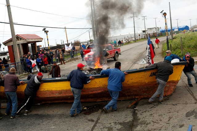 Fishermen block a road with a boat during a protest calling on the government to help ease the economic effects of a harmful algal bloom that had affected their livelihoods at Ancud on Chiloe island in Chile May 5, 2016. (Photo by Pablo Sanhueza/Reuters)