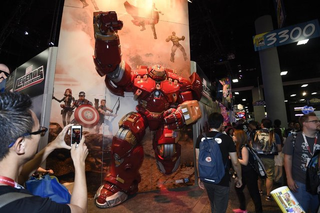 Fans take photos of the Marvel Legend booth on Preview Night at Comic-Con International held at the San Diego Convention Center Wednesday, July 8, 2015, in San Diego. (Photo by Denis Poroy/Invision/AP Photo)