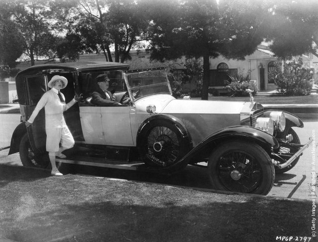 1929: Mae Murray, the radiant Hollywood film star and actress signed by MGM. Seen about to board her Rolls Royce