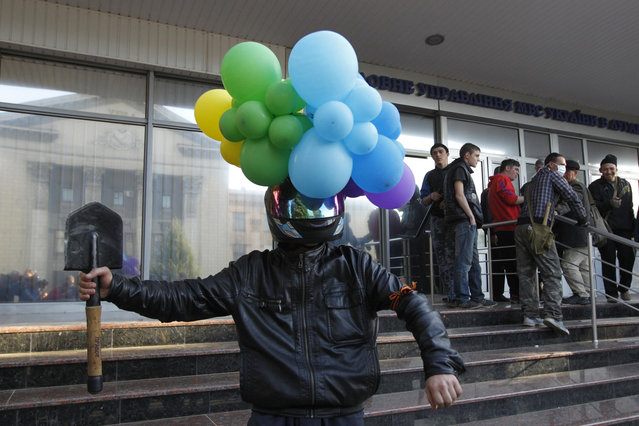A man with balloons attached to his helmet poses for a picture as pro-Russian activists hold a rally near the headquarters of the regional interior ministry to demand the resignation of its head Anatoly Naumenko in Luhansk, eastern Ukraine, May 7, 2014. (Photo by Valentyn Ogirenko/Reuters)