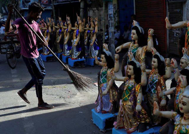 A man cleans a road next to idols of Lord Vishwakarma, the Hindu deity of architecture and machinery, kept on display for sale ahead of the Vishwakarma festival in Kolkata, India, September 17, 2019. (Photo by Rupak De Chowdhuri/Reuters)