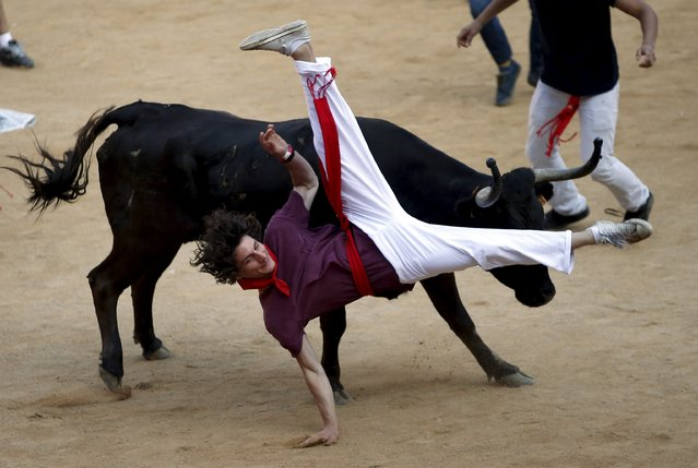 A wild cow charges at a reveller after the sixth running of the bulls of the San Fermin festival in Pamplona, northern Spain, July 12, 2015. Two runners were injured in the run that lasted two minutes and twenty seven seconds, according to local media. (Photo by Susana Vera/Reuters)