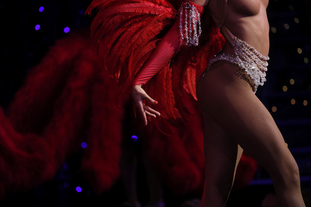 """A dancer performs in the review """"Feerie"""" at the Moulin Rouge in Paris, France, July 23, 2018. Pink and black thigh-high leather boots, with sequin decoration, hang from racks. Elaborate constructions which go over the dancer's shoulders and create the illusion they have sparkling butterfly wings and ostrich feathers sprouting from their backs, sit in rows on tables. (Photo by Philippe Wojazer/Reuters)"""