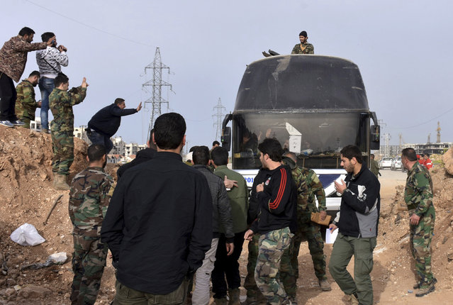 In this photo released by the Syrian official news agency SANA, Syrian government forces welcome a bus carry Syrian citizens and pro-government fighters who evacuated from the two pro-government villages of Foua and Kfarya, upon their arrival at a cross point between the rebels and the Syrian government forces on the outskirts of Aleppo city, Syria, Friday, April, 21, 2017. Syrian state TV says the troubled population transfers involving thousands of Syrians have resumed after stalling for days following a massive explosion that killed dozens. (Photo by SANA via AP Photo)