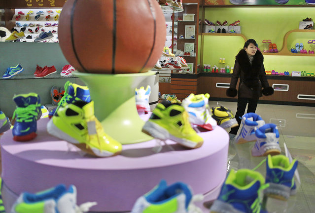 In this Friday, February 1, 2019, photo, a guide stands near a basketball shoe display in a product exhibition room at the Ryuwon Shoe Factory that specializes in sports footwear, in Pyongyang, North Korea. (Photo by Dita Alangkara/AP Photo)