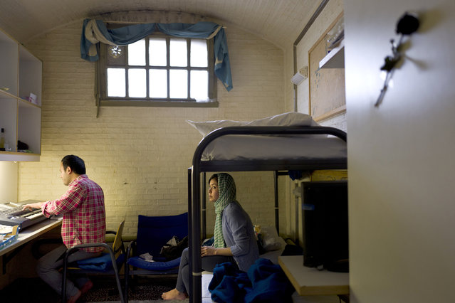 In this Wednesday, April 6, 2016 photo, Afghan refugee Hamed Karmi, 27, plays keyboard next to his wife Farishta Morahami, 25, sitting on a bed inside their room at the former prison of De Koepel in Haarlem, Netherlands. The government has let Belgium and Norway put prisoners in its empty cells and now, amid the huge flow of migrants into Europe, several Dutch prisons have been temporarily pressed into service as asylum seeker centers. (Photo by Muhammed Muheisen/AP Photo)