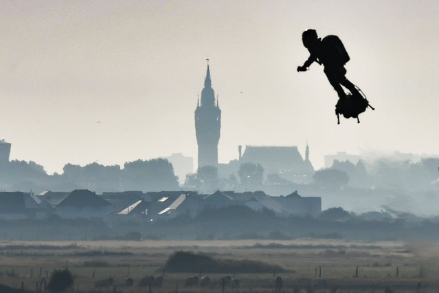 "Franky Zapata on his jet-powered ""flyboard"" flies past the belfry of the city hall of Calais (C) after he took off from Sangatte, northern France, on August 4, 2019, during his attempt to fly across the 35-kilometre (22-mile) Channel crossing in 20 minutes, while keeping an average speed of 140 kilometres an hour (87 mph) at a height of 15-20 metres (50-65 feet) above the sea. Frenchman who has spent years developing a jet-powered hoverboard will again try to zoom across the English Channel on August 4, after a first attempt last month was cut short when a botched refuelling attempt sent him into the water. (Photo by Denis Charlet/AFP Photo)"