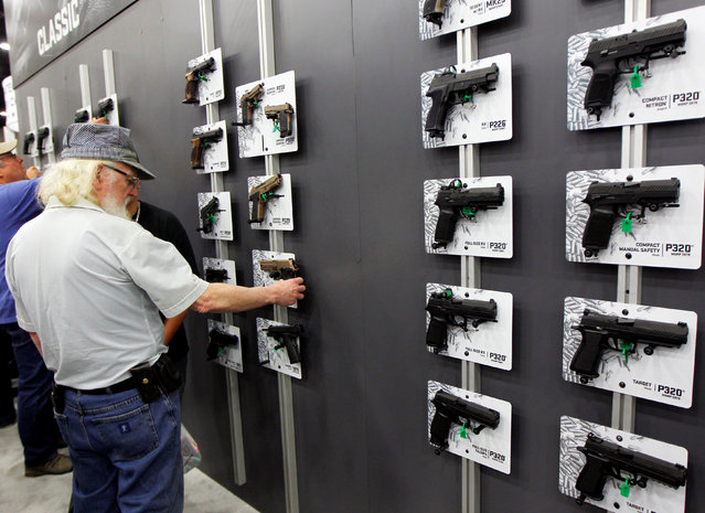 Gun enthusiasts look over Sig Sauers guns at the National Rifle Association's annual meetings & exhibits show in Louisville, Kentucky, May 21, 2016. (Photo by John Sommers II/Reuters)