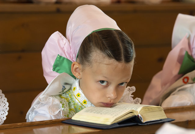 A child dressed in the traditional clothes of the Sorbs attend a holy mass during a Corpus Christi procession in Crostwitz, Germany, Thursday, June 20, 2019. The catholic faithful Sorbs are acknowledged as a national minority near the German-Polish border with their own language in eastern Germany. The procession to commemorate the solemnity of the body and blood of Christ has been a tradition in Lusatia (Lausitz) region. (Photo by Jens Meyer/AP Photo)