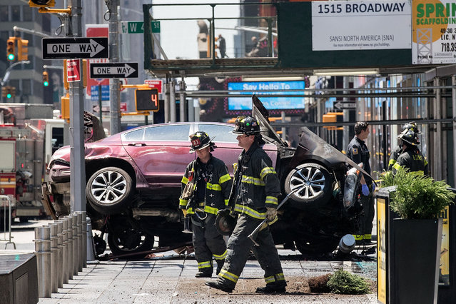 Firefighters walk past a wrecked car in the intersection of 45th and Broadway in Times Square, May 18, 2017 in New York City. According to reports there were multiple injuries and one fatality after the car plowed into a crowd of people. (Photo by Drew Angerer/Getty Images)
