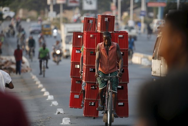 A man transports crates on his bicycle in Burundi's capital Bujumbura, July 22, 2015, as the country awaits the results of yesterday's presidential elections. Opposition politicians have accused Burundi's President Pierre Nkurunziza of violating the constitution by running for a third term and boycotted Tuesday's election in the world's third poorest country. (Photo by Mike Hutchings/Reuters)