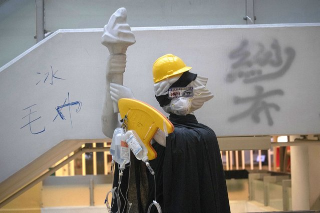 "A statue of the Goddess of Democracy is dressed up with helmet, shield and drip bags at a first aid counter setup for possible injuries in the Hong Kong Polytechnic University in Hong Kong on Sunday, November 17, 2019. Most anti-government protesters left Hong Kong's universities Saturday after occupying them for about a week. Small contingents that remained harassed some of those cleaning up and kept a major cross-harbor tunnel closed. Words on wall reads ""Bandage"", ""Ice"" and ""Towel"". (Photo by Ng Han Guan/AP Photo)"