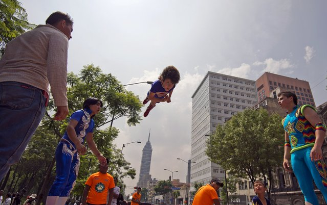 Circus' workers perform as they take part in a protest against a law which prohibits the use of animals in their shows, in Mexico City on June 10, 2014. The law was approved Monday by the local assembly of Mexico City. (Photo by Alfredo Estrella/AFP Photo)