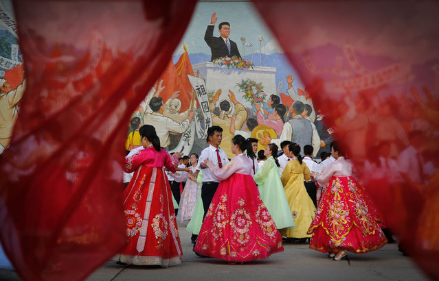 Students participate in a mass dance in front of a mural of the late North Korean leader Kim Il Sung delivering a speech, Monday, July 27, 2015, in Pyongyang, North Korea as part of celebrations for the 62nd anniversary of the armistice that ended the Korean War. (Photo by Wong Maye-E/AP Photo)