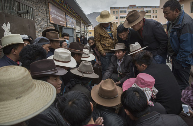 Tibetan nomads crowd around as they bid on cordycep fungus for sale at a market on May 22, 2016 on the Tibetan Plateau in Yushu town in the Yushu Tibetan Autonomous Prefecture of Qinghai province. (Photo by Kevin Frayer/Getty Images)