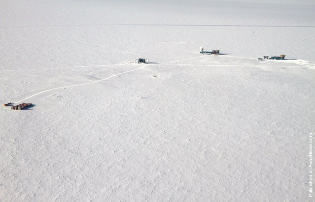 """The """"Dark Sector"""" at Amundsen-Scott South Pole Station is so named due to the absence of radio and light wave interference for the telescopes located there. The buildings on the left are the IceCube drill site facilities. The next building is the Ice Cube Laboratory (ICL). The third building is the Dark Sector Lab (DSL) with the South Pole Telescope and Bicep II Telescope. The building at right is the Martin A. Pomerantz Observatory (MAPO). Photo taken on February 3, 2011"""