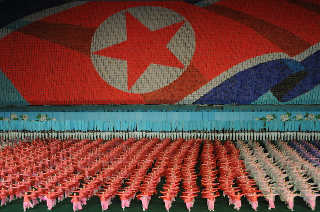 """""""The Mass Games"""". Tens of thousands of performers take part in the Arirang Mass Games held each year in Pyongyang. Each pixel in the backdrop is a schoolchild holding a book of coloured pages, turned on command to display patriotic images telling the history of the nation. Thousands of dancers form the foreground, all moving in perfectly choreographed uniformity. Photo location: May Day Stadium, Pyongyang, Democratic People's Republic of Korea. (Photo and caption by Nicola Chilton/National Geographic Photo Contest)"""