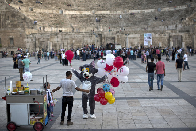 A Jordanian man wearing a costume sells balloons at the ancient Roman Theater in Amman, Jordan, Friday, July 31, 2015. (Photo by Muhammed Muheisen/AP Photo)