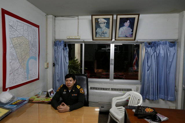 A firefighter sits at his office which is decorated with pictures of Thailand's King Bhumibol Adulyadej and Queen Sirikit in Bangkok, Thailand, June 4, 2016. (Photo by Jorge Silva/Reuters)