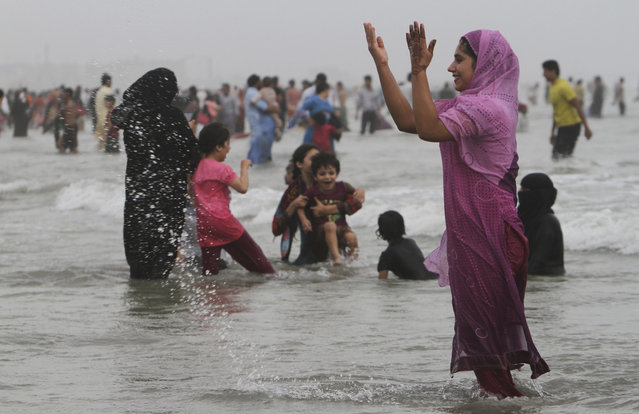 People enjoy at Clifton beach in Karachi, Pakistan, during a warm weather on Wednesday, July 22, 2015. (Photo by Farid Khan/AP Photo)
