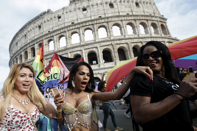 People march past the Colosseum during the Gay Pride parade in Rome, Saturday, June 11, 2016. Italy joined the rest of Europe last month in giving some legal rights to gay couples after a years-long battle and opposition from the Catholic Church to anything that smacked of authorizing gay marriage. (Photo by Fabio Frustaci/AP Photo)