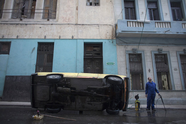Mechanic Carlos Rodriguez, 29, calls to relatives to open the water for his high-pressure cleaner, as he washes the bottom of a Russian-made Moscovich car in downtown Havana, February 19, 2015. (Photo by Alexandre Meneghini/Reuters)