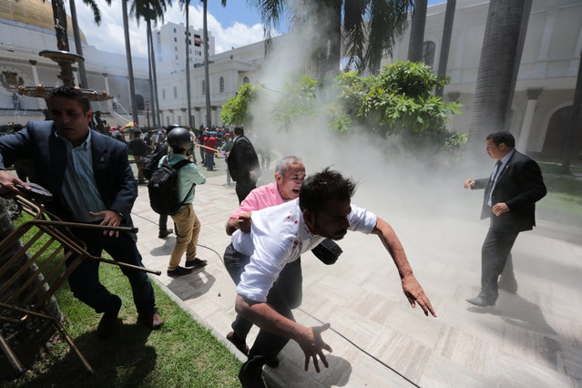 National Assembly workers, center and left, run from an attack by pro-government militia members attacking opposition lawmakers and assembly employees during a special session coinciding with Venezuela's independence day, in Caracas, Venezuela, Wednesday, July 5, 2017. At right is opposition congressperson Simon Calzadilla. (Photo by Fernando Llano/AP Photo)