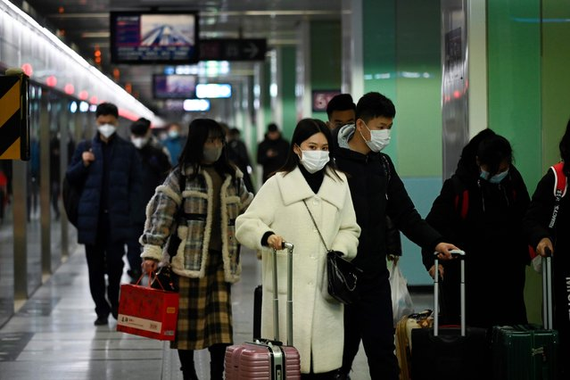 People wearing protective masks walk at a subway station in Beijing on January 22, 2020. A new virus that has killed nine people, infected hundreds and already reached the United States could mutate and spread, China warned January 22, as authorities scrambled to contain the disease during the Lunar New Year travel season. (Photo by Wang Zhao/AFP Photo)