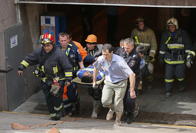 "Russian rescue workers transport an injured passager to an ambulance from ""Park Pobedy"" metro station, where three carriages derailed in Mocow, Russia, July 15, 2014. (Photo by Yuri Kochetkov/EPA)"