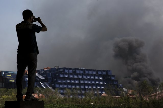 A man takes pictures at the explosion site in Binhai new district in Tianjin, China August 13, 2015. (Photo by Damir Sagolj/Reuters)