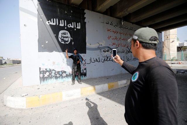 A member of Iraqi counterterrorism forces use his phone to take a picture in Falluja, Iraq, June 26, 2016. (Photo by Thaier Al-Sudani/Reuters)