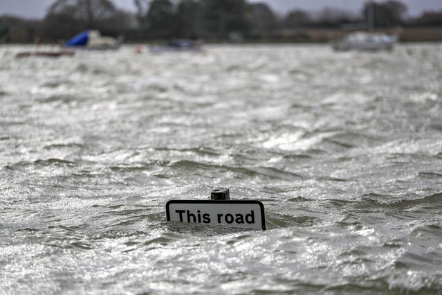 A street sign is seen under flood water in Bosham caused by the high tide, in England, Monday, February 10, 2020. Storm Ciara battered the U.K. and northern Europe with hurricane-force winds and heavy rains Sunday, halting flights and trains and producing heaving seas that closed down ports. Propelled by the fierce winds, a British Airways plane was thought to have made the fastest New York-to-London flight by a conventional airliner. (Photo by Steve Parsons/PA Wire via AP Photo)