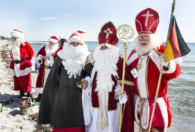 Santas from all over the world gather for the traditional July Santa Congress in Copenhagen Tuesday, July 22, 2014 and stuck to their traditional schedule reserving half the day for a a dip in the sea – although, their feet only – in the waters of Oresund, the sound between Copenhagen and the Swedish Coast. (Photo by Mogens Flindt/AP Photo/Polfoto)