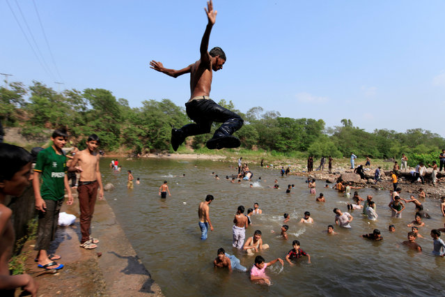 A man jumps in to a stream to cool off from the heat on a hot summer day in Islamabad, Pakistan, June 30, 2016. (Photo by Faisal Mahmood/Reuters)