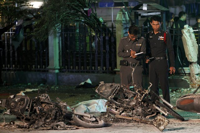 Experts investigate the remains of destroyed motorcycles at the Erawan shrine, the site of the blast in central Bangkok August 17, 2015. (Photo by Kerek Wongsa/Reuters)