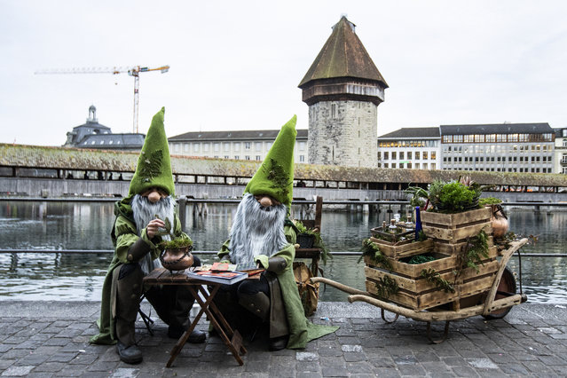 Costumed revelers pose in front of the Chapell bridge on the opening day of the carnival in Lucerne, Switzerland, 20 February 20​20. The carnival takes place in Lucerne from 20 to 25 February 2020. (Photo by Alexandra Wey/EPA/EFE)