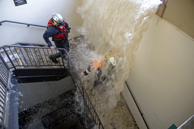 Workers walk down stairs to a parking structure as water cascades down on them on the UCLA campus after flooding from a broken 30-inch water main under nearby Sunset Boulevard inundated a large area of the campus in the Westwood section of Los Angeles, Tuesday, July 29, 2014. (Photo by Mike Meadows/AP Photo)