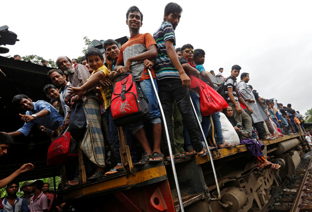 People stand on an engine of an overcrowded passenger train as they travel home to celebrate Eid al-Fitr festival, which marks the end of the Muslim holy fasting month of Ramadan, at a railway station in Dhaka, Bangladesh, July 5, 2016. (Photo by Adnan Abidi/Reuters)