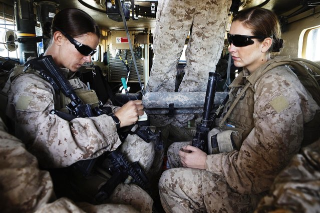 U.S. Marine and Female Engagement Team leader Sgt. Sheena Adams (L) and H.N. Shannon Crowley from First Battalion, Eighth Marines sit in an armored vehicle before heading out on an operation from their base at Musa Qala in southern Afghanistan's Helmand province, November 13, 2010. (Photo by Finbarr O'Reilly/Reuters)