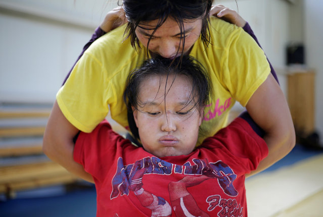 Mongolia's Olympic wrestler Battsetseg Soronzonbold (top) helps her teammate Cantuya Enkhbat stretch during a daily training session at the Mongolia Women's National Wrestling Team training centre in Bayanzurkh district of Ulaanbaatar, Mongolia, July 1, 2016. (Photo by Jason Lee/Reuters)