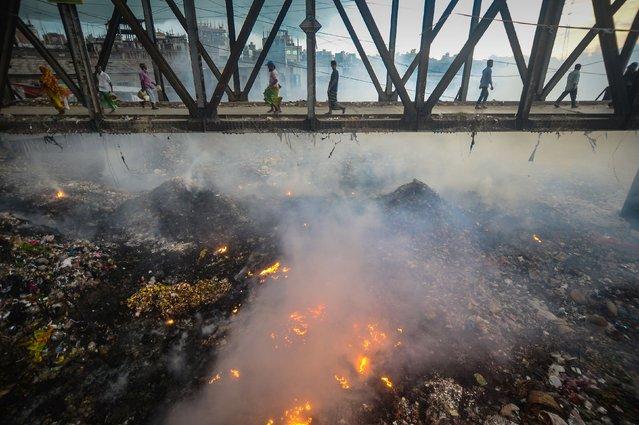Bangladeshi pedestrians cross an iron bridge as smoke rises from a fire in a garbage dump below them near the Buriganga river in Dhaka on June 11, 2017. (Photo by Munir Uz Zaman/AFP Photo)