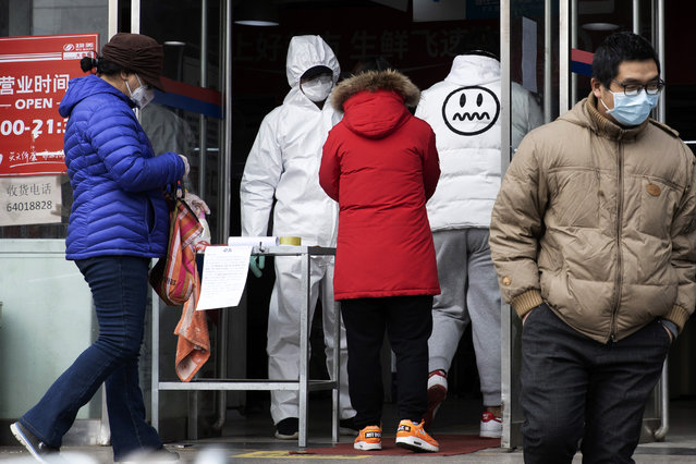 A worker in overalls screen for fever at the entrance to a supermarket in Beijing Thursday, February 27, 2020. South Korea and China each reported hundreds more virus cases Thursday as the new illness persists in the worst-hit areas and spreads beyond borders. (Photo by Ng Han Guan/AP Photo)