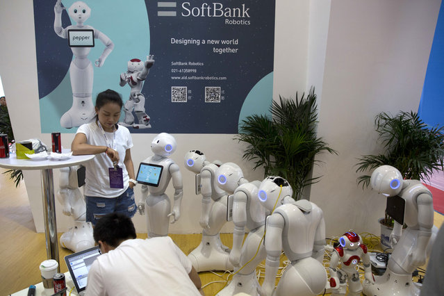 A robot looks up to its human minder as other powered down robot wait to be activated a day before the opening of the World Robot Conference held in Beijing, China, Tuesday, August 22, 2017. (Photo by Ng Han Guan/AP Photo)