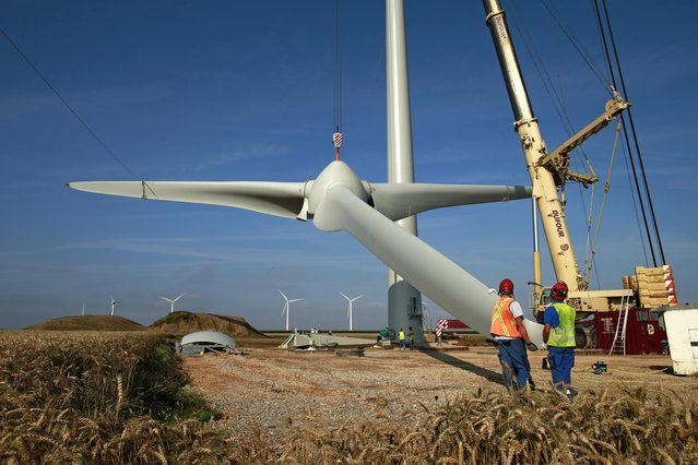 Employees control the lifting of the rotor hub of an E-70 wind turbine manufactured by German company Enercon for La Compagnie du Vent (GDF SUEZ Group) during its installation at a wind farm in Meneslies, Picardie region, July 31, 2014. France announced in July a package of tax breaks and low-cost loans to improve insulation in buildings and boost investment in renewable energy, which is supposed to provide 40 percent of the country's electricity by 2030. (Photo by Benoit Tessier/Reuters)