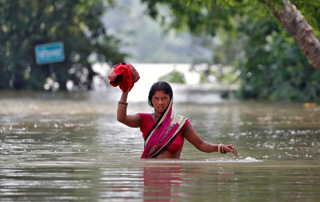 A woman wades through a flooded village in the eastern state of Bihar, India August 22, 2017. (Photo by Cathal McNaughton/Reuters)