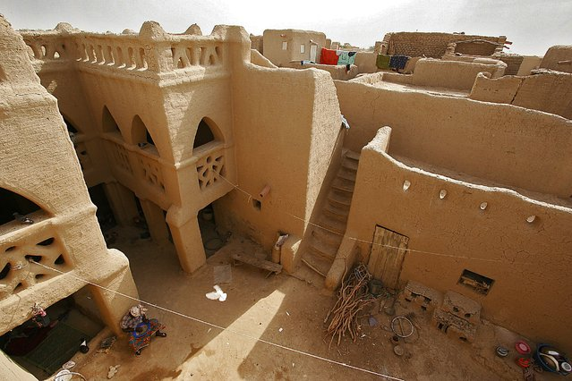 This file photo taken on February 9, 2005 shows a woman resting in the courtyard of a large earthen mud house, in Djenne, in the Niger Delta region in central Mali. The old towns of Djenne, 570 kilometres (350 miles) northeast of the Malian capital Bamako, have been inhabited since 250 BC and are characterised by the extraordinary use of earth in their architecture. UNESCO said that the 40th meeting of its World Heritage Committee in Istanbul decided to place the site on its list of world heritage in danger. (Photo by François Xavier/AFP Photo)